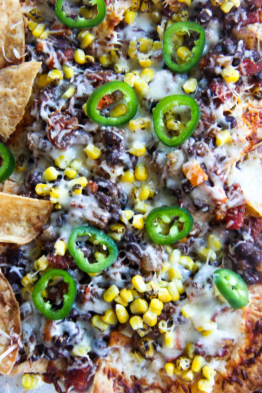 These Sheet Pan Black Bean Chili Nachos is an easy dinner or the ultimate party snack — you choose! Crispy, crunchy, salty, packed with flavor, and vegetarian-friendly.