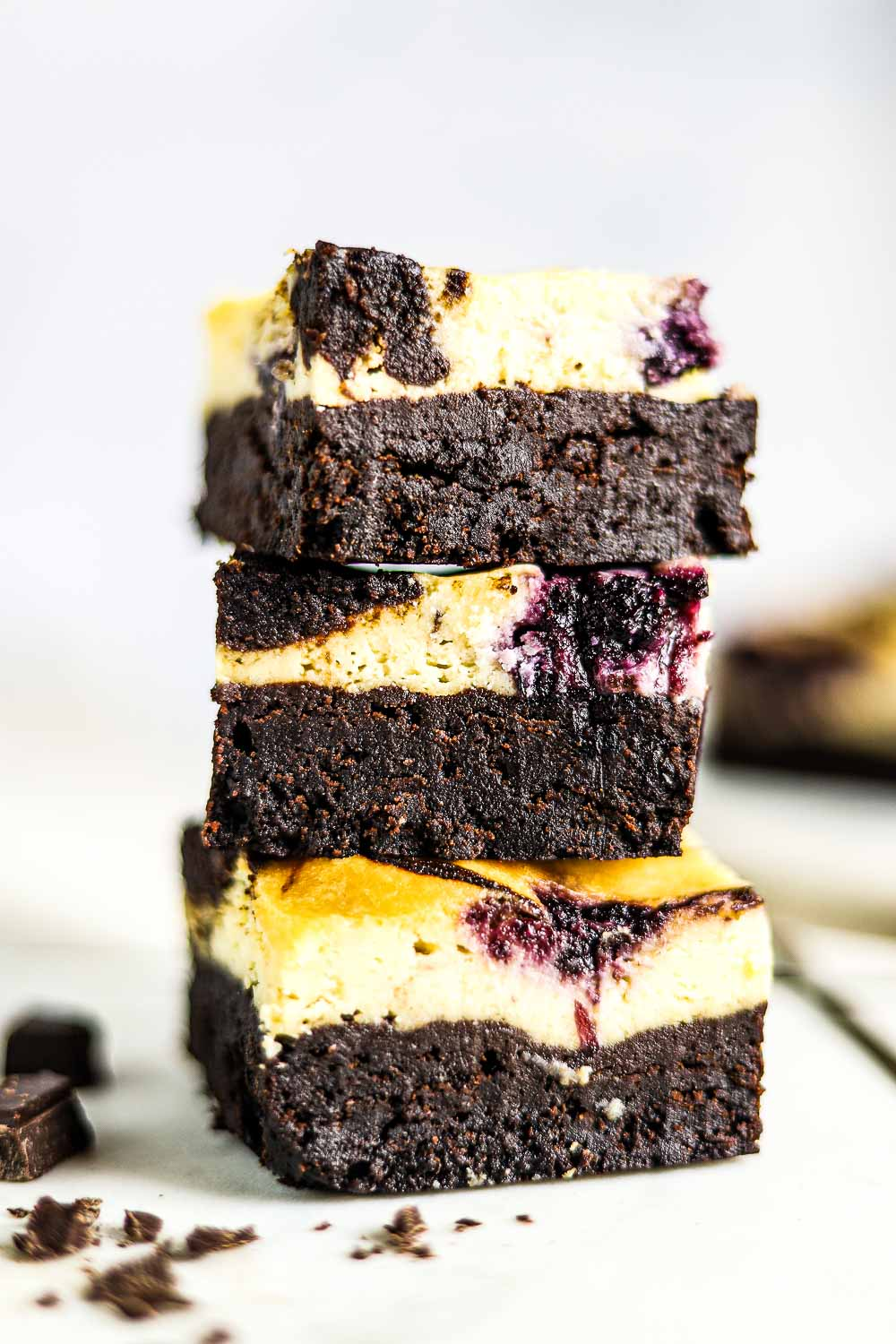 These Blueberry Swirl Cheesecake Brownies are so delicious that they are going to make your head spin! It is a decadent layered dessert that starts with the perfect brownie and topped with a layer of blueberry swirl cheesecake!